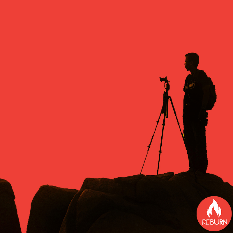 man standing on a mountain taking photos or videos for content creation as reburn marketing provides social media marketing and social media management